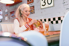 Mature woman eating burger in 1950's diner