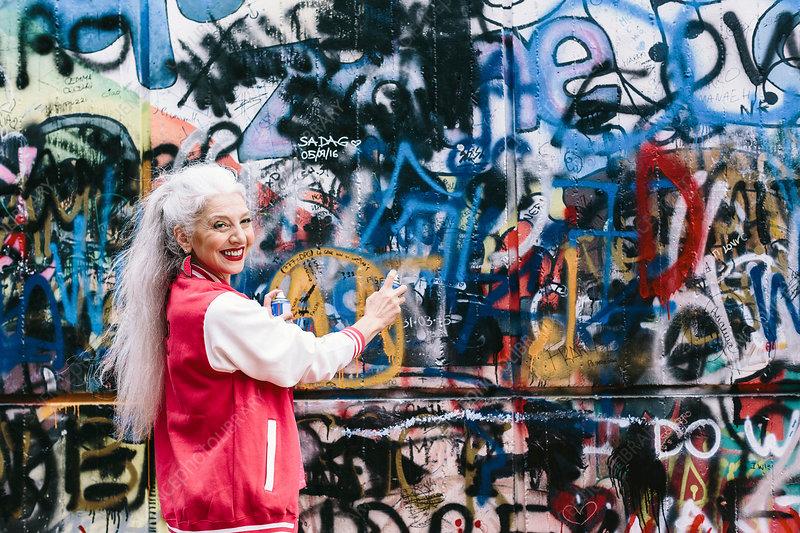 Mature woman spray painting graffiti wall