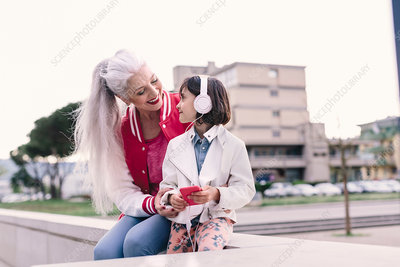 Mature woman and girl listening to headphone