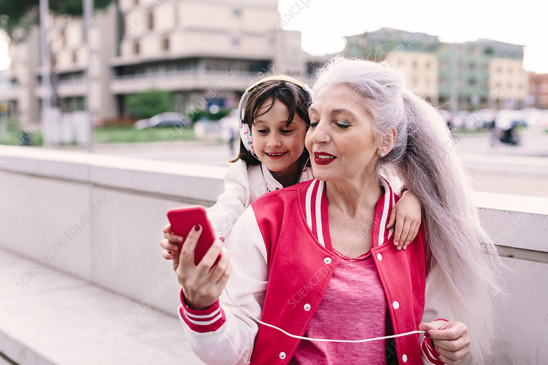 Mature woman and girl selecting headphone music in city