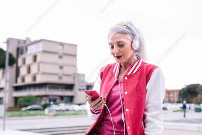 Mature woman in baseball jacket listening to headphones
