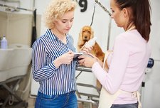 Female groomer taking customer credit card payment