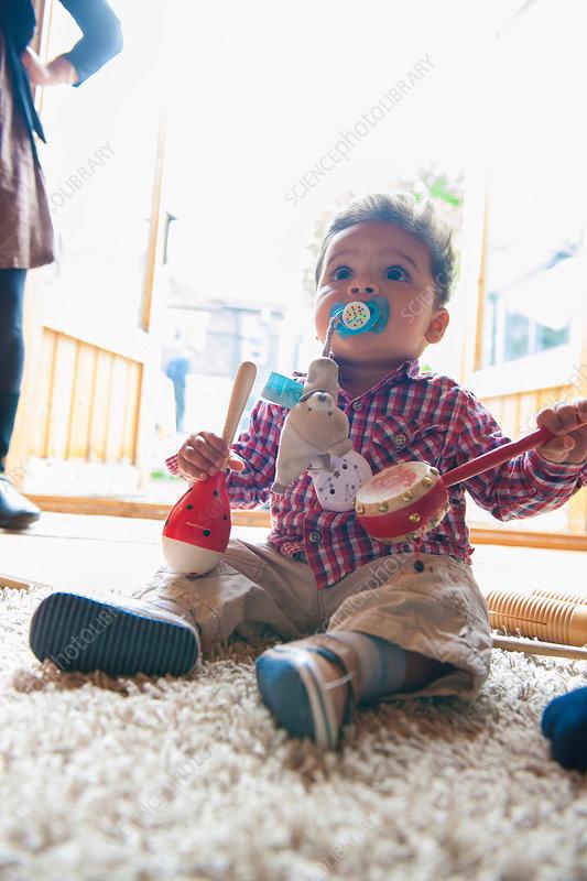 Baby boy holding maracas