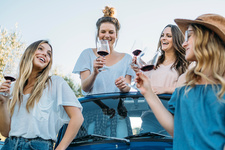 Friends drinking wine in convertible car, Firenze, Italy