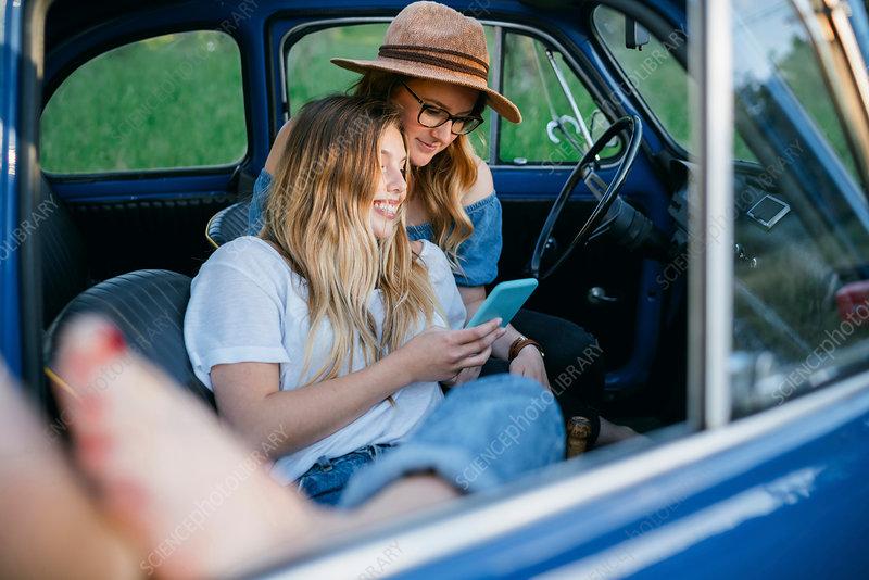 Friends sitting in car using digital tablet, Firenze, Italy