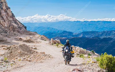 Man driving on touring motorbike on dirt road, Bolivia