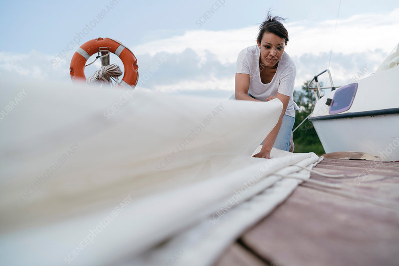 Young woman folding boat's sail