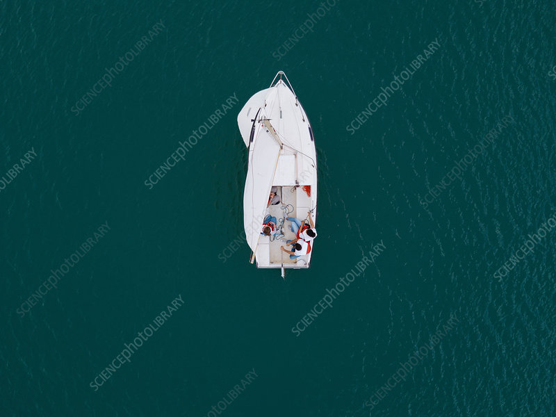 Group of people on sailing boat on lake, overhead view