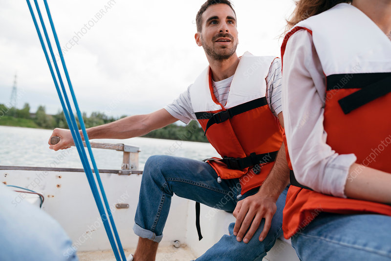Man and woman on sailing boat, man steering boat