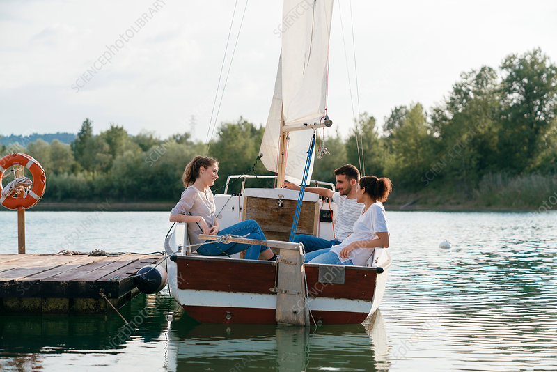 Three friends relaxing on sailing boat on lake