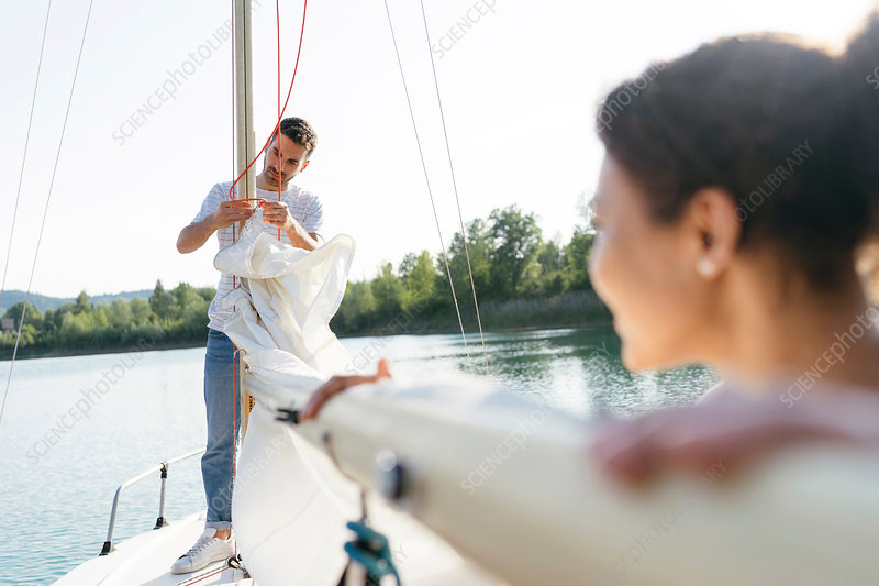Man on sailing boat, taking down sail