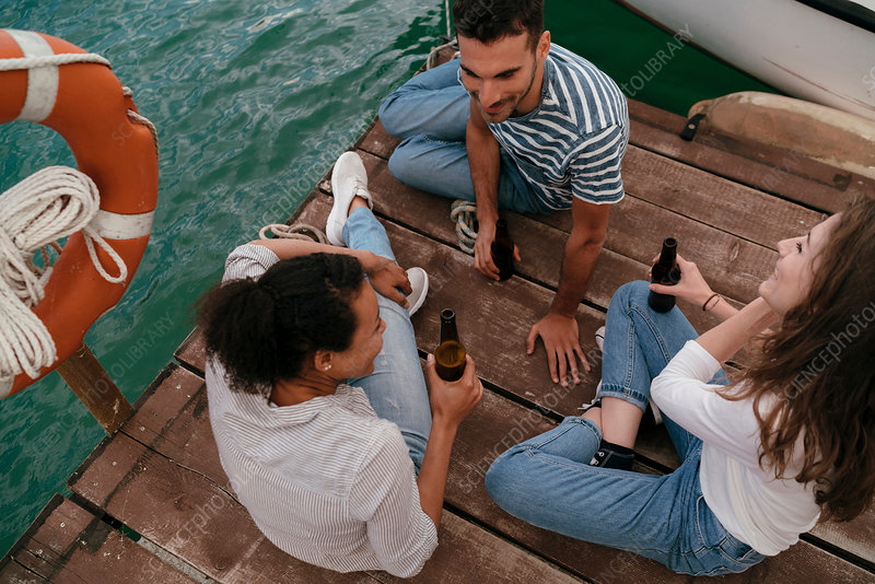 Three friends relaxing on pier