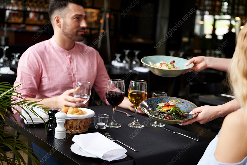 Waitress serving lunch to couple at restaurant table