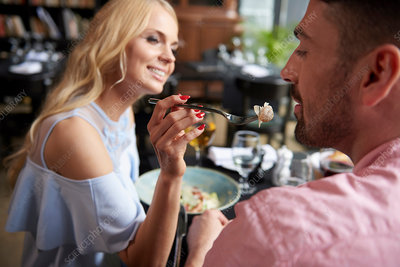 Young woman feeding boyfriend lunch at restaurant table