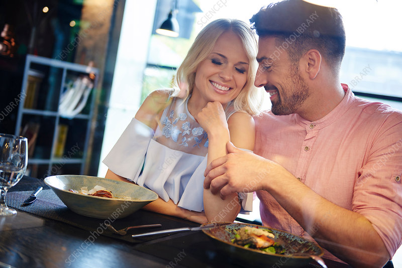 Man touching girlfriend's arm at restaurant table