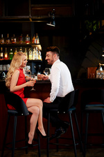 Glamorous couple laughing while sitting at bar