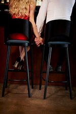 Rear view of couple holding hands while sitting at bar