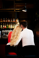 Rear view of romantic couple sitting at bar