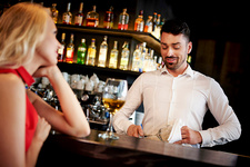 Barman flirting with young woman sitting at bar