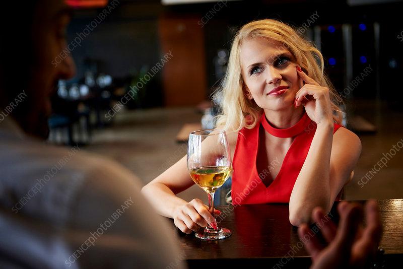 Young woman flirting with barman sitting at bar