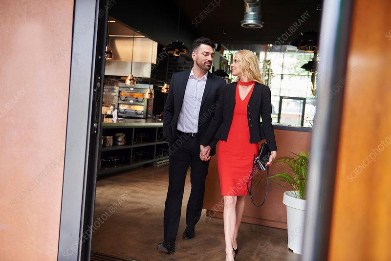 Glamorous couple leaving restaurant