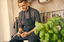 Chef in kitchen looking at smartphone smiling