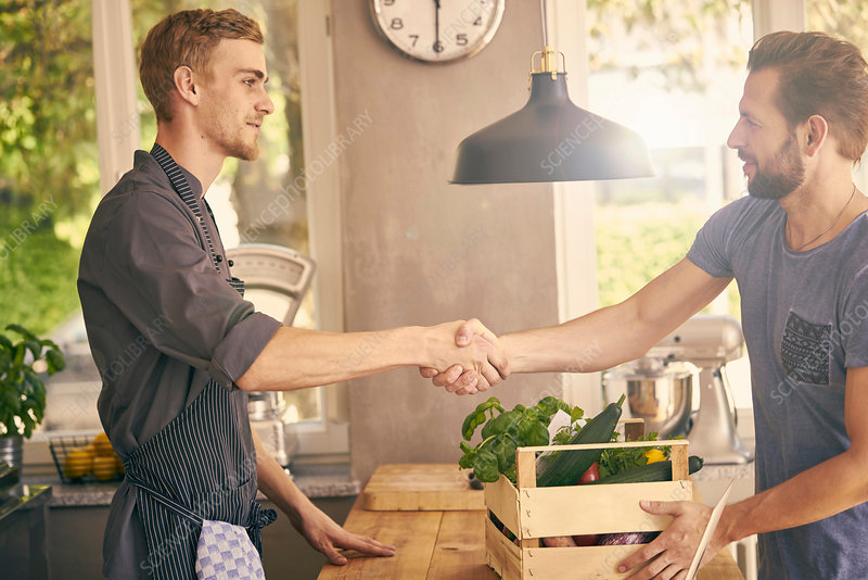 Chef and vegetable delivery man shaking hands
