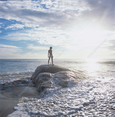 Man standing on rock in sea looking away, Sri Lanka