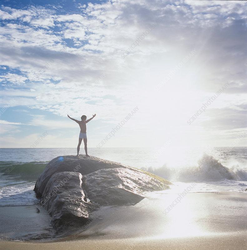 Man standing on rock in sea looking away, Sri Lanka