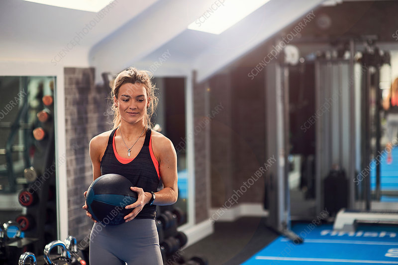 Young woman training, holding atlas ball in gym