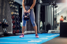 Waist down view of young woman holding kettle bell in gym