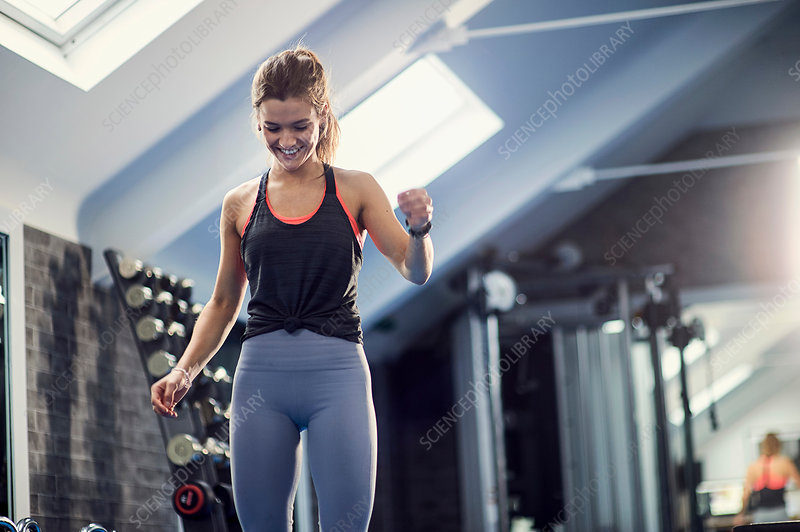 Happy young woman training, looking down in gym