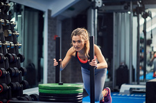 Young woman training, pushing weight sled in gym