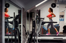 Young woman training, running on gym treadmill