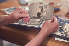 Hands of senior woman holding old photograph