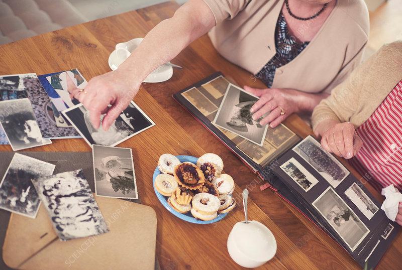 Senior women looking at old photographs at table