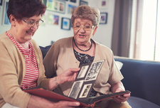 Two senior women on sofa looking at old photograph album