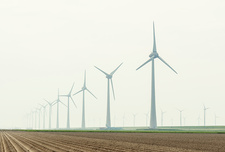 Row of wind turbines in field dyke landscape