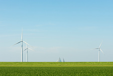 Wind turbines in field landscape with ship sails on horizon