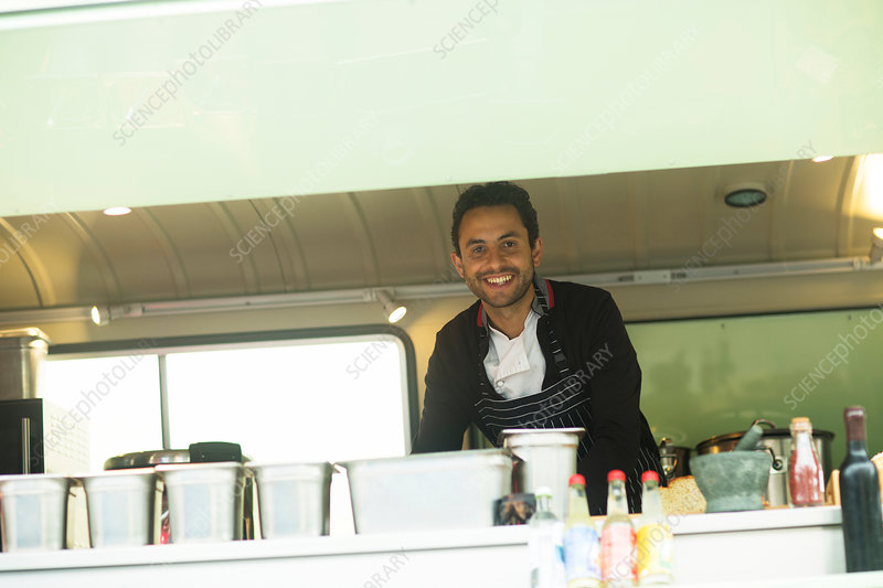 Portrait of small business owner at food truck hatch