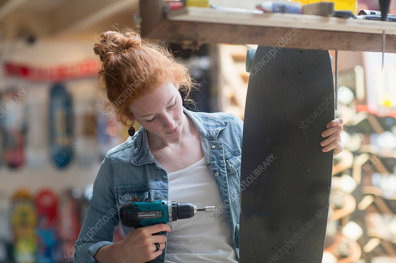 Woman working, using hand tool to remove skateboard wheel