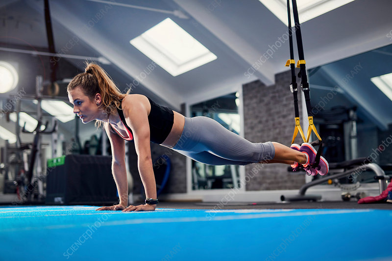 Young woman doing push ups using exercise handles in gym