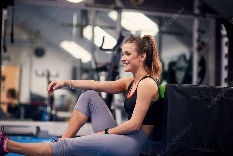 Happy young woman training, sitting on gym floor