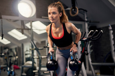 Young woman holding kettle bells in gym