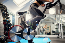 Neck down view of woman pedalling exercise bike