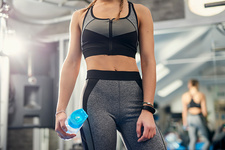 Mid section of woman training, holding water bottle in gym