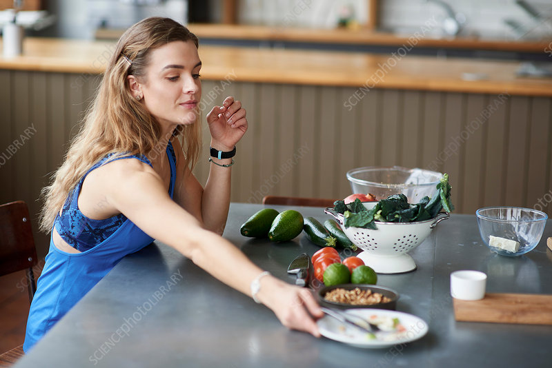 Young woman at kitchen table with finished salad plate