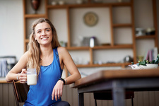 Young woman at kitchen table with smoothie