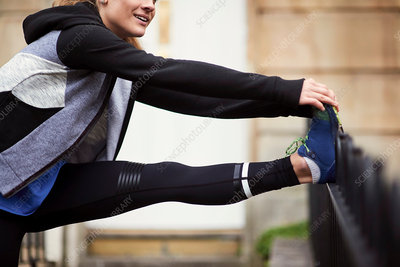 Young female runner outside front door touching toes