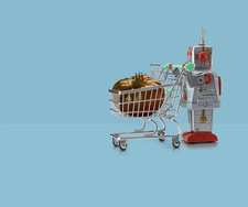 Toy robot pushing miniature shopping trolley with tomato